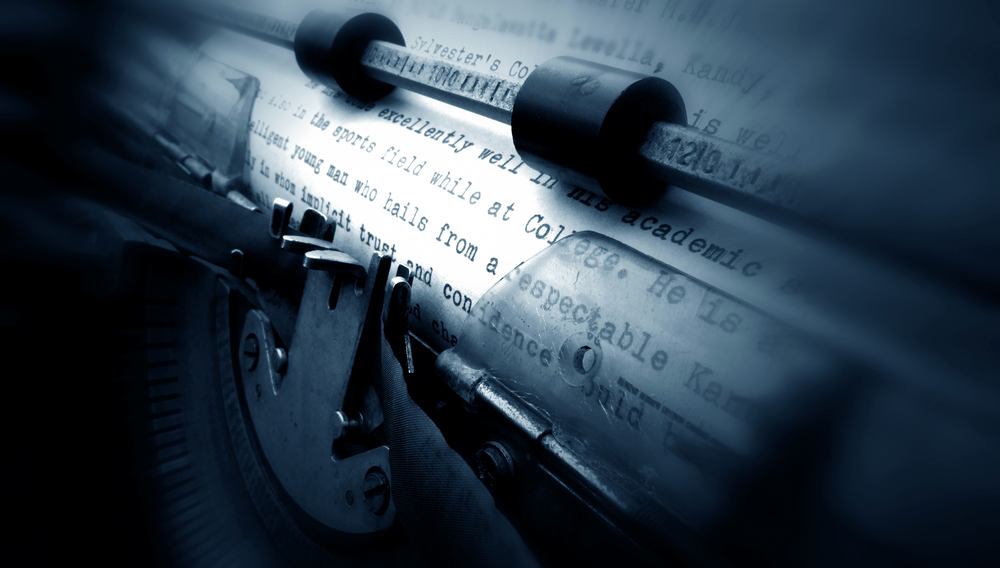 """Closeup picture of an old manual typewriters' platen. There is a paper on the roll with typing about an """"intelligent young man who does excellently well""""."""