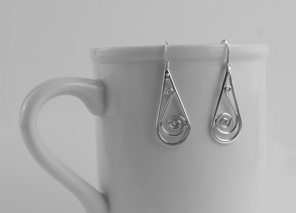 Picture of sterling teardrop shape wire scroll, or spiral dangles hanging from the edge of a white coffee mug. Has handmade french wires.