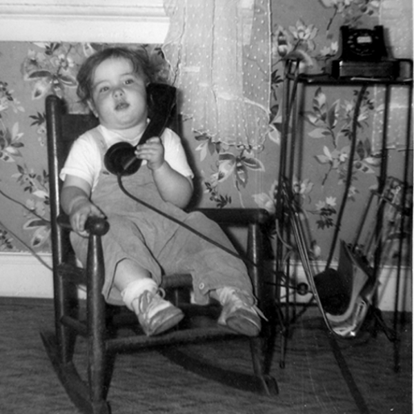 Old picture of baby Pam talking on a rotary telephone. She is sitting in a rocking chair.