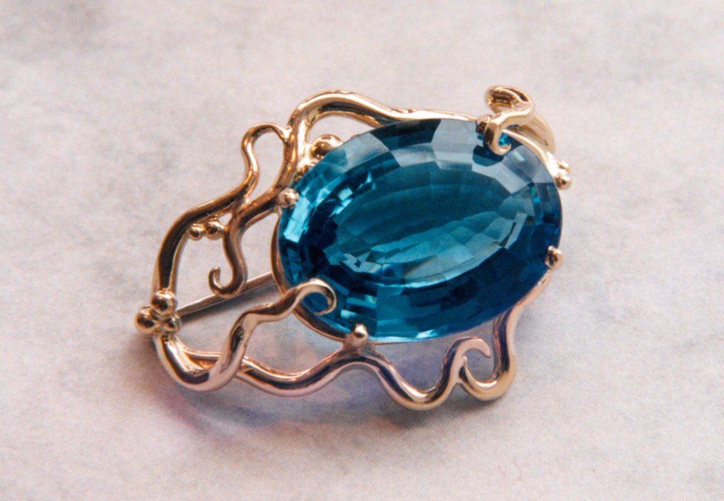 14KY gold blue topaz pin. Stone is surrounded by gold vines.