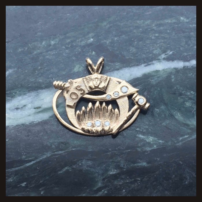 This is a picture of a 14 karat gold and diamond Past High Priestess pendant. It is sitting on a polished Vermont Serpentine slab.