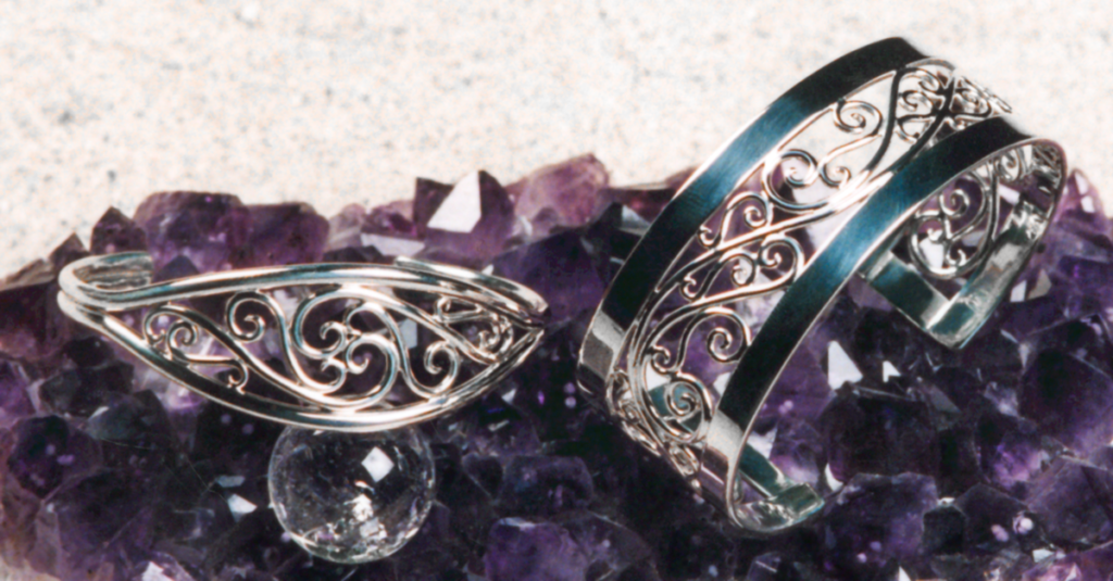 Picture of 2 sterling scroll bracelets on an Amethyst cluster