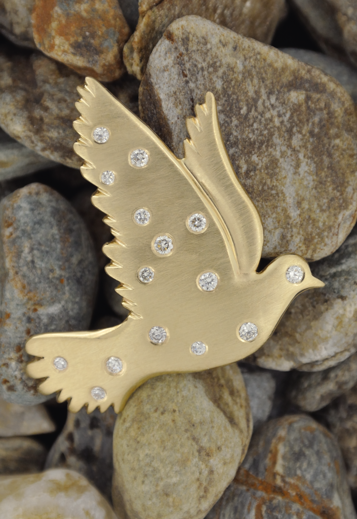 A picture of the 14K karat yellow and diamonds dove pin. It is resting on a background of Vermont river rocks.