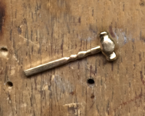 Picture of a gold gavel, prior to sanding and polishing, It is resting against a wood bench pin.